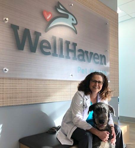 Principal Doctor Deborah Capper, DVM, holding a dog